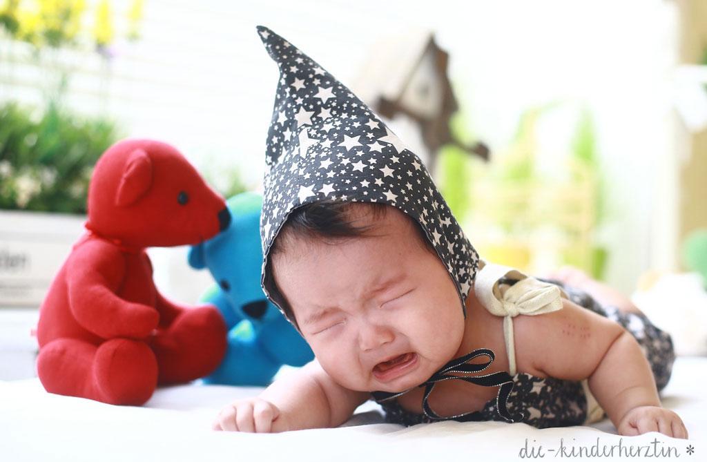 Fieber bei Kindern weinendes Kind neben Stofftieren