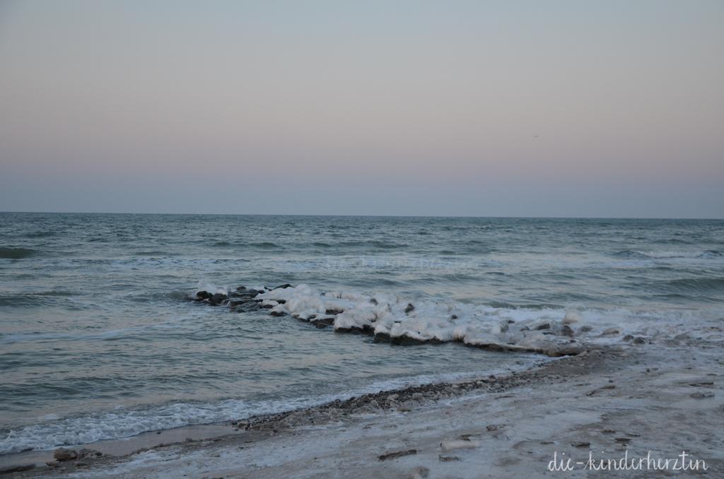 Winterwunderstrand Lübecker Bucht Strand Wellen vereiste Steine unter pastellfarbenem Himmel