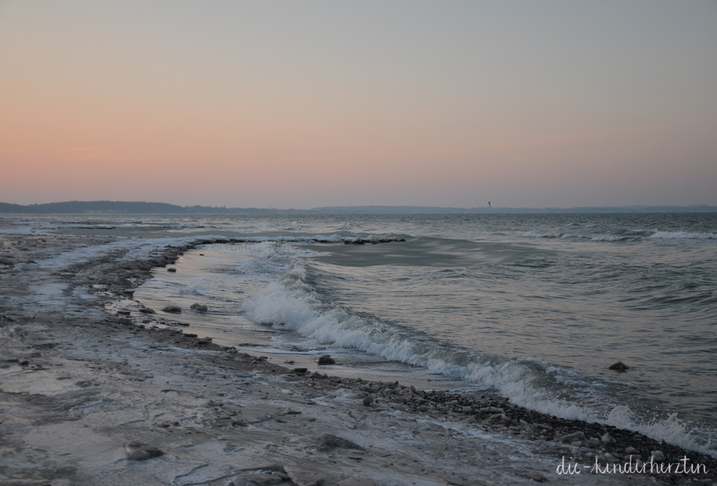 Winterwunderstrand Lübecker Bucht vereister Strand Wellen Sonnenuntergang