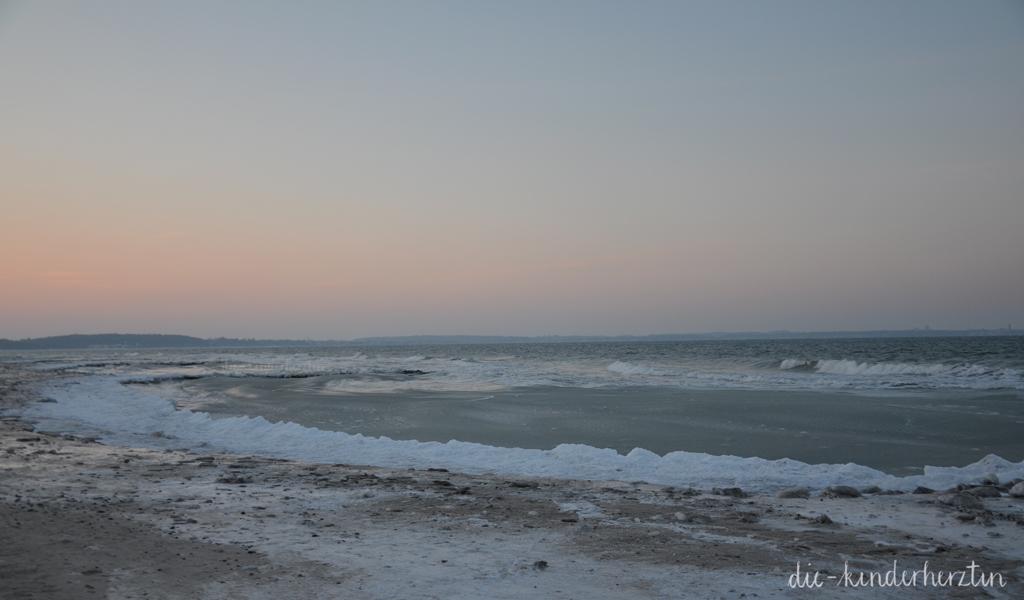 Winterwunderstrand Lübecker Bucht Strand Wellen Schnee unter pastellfarbenem Himmel