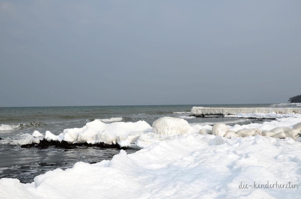 Ostsee im Schnee- und Eisgewand, Gefrorener Steg und Steine am Meer, verschneiter Küste